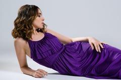 Härlig brunett i den violetta klänningen Arkivbild