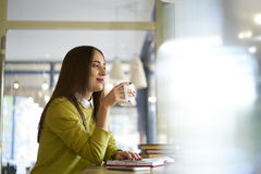 Härlig brunett i en gul blus som noterar bästa idéer att diskutera på möte med anställd, medan tycka om kaffe Arkivfoto