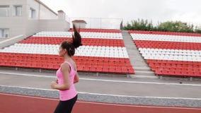 Härlig brunett i en rosa T-tröja som kör ner trampkvarnen på stadion lager videofilmer