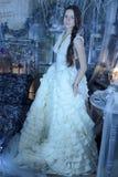 Härlig brunett i en vit klänning i tappninginre royaltyfria foton