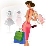 Härlig brunett i ett rött klänninganseende nära shoppa Royaltyfria Bilder