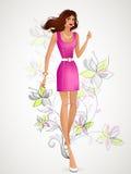Härlig brunett i ett rosa klänninganseende på bakgrunden Co Fotografering för Bildbyråer