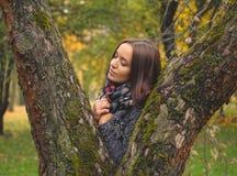 Härlig brunett i halsduk i höstdag Härlig brunett som poserar i trädstam i halsduk i höstdag royaltyfria foton
