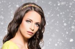 Härlig brunett med den lyxiga guld- halsbandet över vinterbackg Arkivfoto