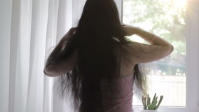 Härlig brunett med långt hår vid fönstret En kvinna upplöser, fixar hennes hår sun långsam rörelse stock video