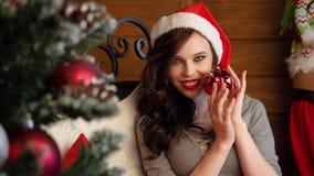 Härlig brunett sexiga Santa Claus i elegant hatt och behå Dana ståenden av modellflickan inomhus med julgranen arkivfilmer