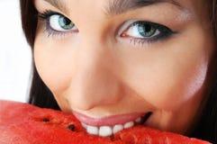 härlig brunett som äter melonen royaltyfria bilder