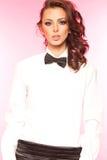 Härlig brunett som bär en smokingpilbåge- och vitskjorta Royaltyfria Foton