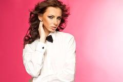 Härlig brunett som bär en smokingpilbåge- och vitskjorta Arkivbild