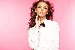 Härlig brunett som bär en smokingpilbåge- och vitskjorta Royaltyfria Bilder