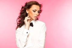 Härlig brunett som bär en smokingpilbåge- och vitskjorta Arkivbilder