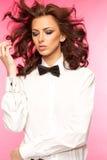 Härlig brunett som bär en smokingpilbåge- och vitskjorta arkivfoton