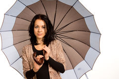 Härlig brunett som bär ett paraply arkivfoton