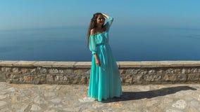 Härlig brunett som ler flickan med sunt långt hår, i att blåsa klänningen Lycklig ung kvinna som tycker om naturen och har arkivfilmer