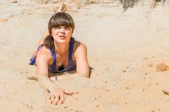 Härlig brunett som ligger på den varma sanden Arkivbilder