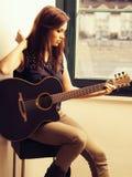 Härlig brunett som spelar den akustiska gitarren Royaltyfri Bild