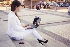 Härlig brunettaffärskvinna i den vita dräkten med anteckningsboken på hennes varv, maskinskrivning som är funktionsduglig utomhus royaltyfri fotografi
