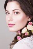 Härlig brunettbrud som ler med naturliga smink- och blommarosor i hennes frisyr Royaltyfri Bild