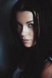 Härlig brunettflicka över mörkerbakgrund fotografering för bildbyråer