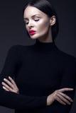 Härlig brunettflicka i en svart klänning, ett rakt hår och en moderiktig makeup Glamourskönhetframsida Royaltyfri Bild