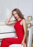 Härlig brunettflicka i en trendig aftonklänning röda kanter härlig för studiokvinna för par dans skjutit barn royaltyfri bild