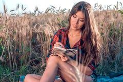 Härlig brunettflicka i fält Läser nya idéer för begrepp, anmärkningar i den nya sommaren i natur I hans hand en anteckningsbok Royaltyfria Foton