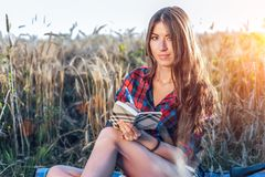 Härlig brunettflicka i fält Nya idéer för begrepp, utomhus, sommar i natur I hans hand en anteckningsbok, långt hår Arkivfoto