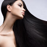 Härlig brunettflicka i flyttning med ett perfekt slätt hår och klassiskt smink Härlig le flicka Royaltyfria Bilder