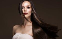 Härlig brunettflicka i flyttning med ett perfekt slätt hår och klassiskt smink Härlig le flicka royaltyfri bild