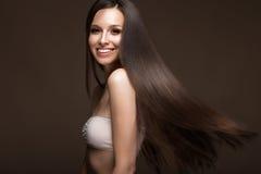Härlig brunettflicka i flyttning med ett perfekt slätt hår och klassiskt smink Härlig le flicka royaltyfri foto