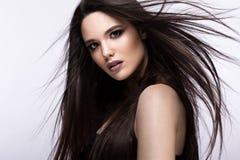 Härlig brunettflicka i flyttning med ett perfekt slätt hår och klassiskt smink Härlig le flicka Fotografering för Bildbyråer