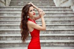 Härlig brunettflicka i röd klänning med lång sund hårposi Royaltyfria Foton
