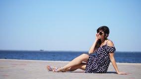 Härlig brunettflicka i solexponeringsglas och sundress, med stor hörlurar som lyssnar till musik från smartphonen, på stranden arkivfilmer