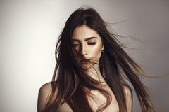 Härlig brunettflicka med att fladdra hår på vind royaltyfria bilder