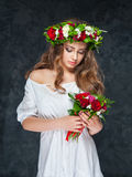 Härlig brunettflicka med en sammansättning av blommor Royaltyfri Foto