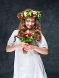 Härlig brunettflicka med en sammansättning av blommor Fotografering för Bildbyråer