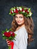 Härlig brunettflicka med en sammansättning av blommor Royaltyfria Bilder
