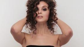 Härlig brunettflicka med ett perfekt lockigt hår och klassiskt smink som poserar i studion Härlig le flicka stock video