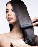 Härlig brunettflicka med ett perfekt slätt hår, krulla och ett klassiskt smink Härlig le flicka royaltyfri foto