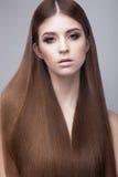 Härlig brunettflicka med ett perfekt slätt hår- och klassikersmink Härlig le flicka royaltyfria bilder