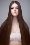 Härlig brunettflicka med ett perfekt slätt hår- och klassikersmink Härlig le flicka royaltyfria foton