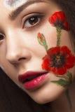 Härlig brunettflicka med krullning och en blom- modell på framsidan Abstrakt naturliga bakgrunder Fotografering för Bildbyråer