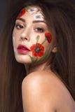 Härlig brunettflicka med krullning och en blom- modell på framsidan Abstrakt naturliga bakgrunder Arkivbilder