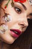 Härlig brunettflicka med krullning och en blom- modell på framsidan Abstrakt naturliga bakgrunder Royaltyfri Foto