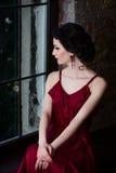 Härlig brunettflicka med sinnlig blick och härliga händer Stående vid fönstret Royaltyfri Foto
