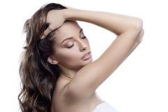 Härlig brunettflicka med sund Hair Tvål-, handduk- och blommasnowdrops Isolerat på vit royaltyfri fotografi