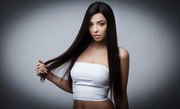 Härlig brunettflicka med sunt långt hår Arkivfoton