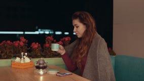 Härlig brunettflicka som dricker kaffe eller te i kafé med kopieringsutrymme stock video