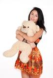 Härlig brunettflicka som kramar en nallebjörn Arkivfoto