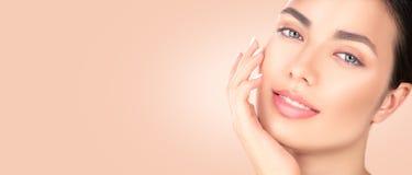 Härlig brunettflicka som trycker på hennes framsida Ren skönhetmodell Spa skönhetstående Ungdom- och skincarebegrepp arkivfoto
